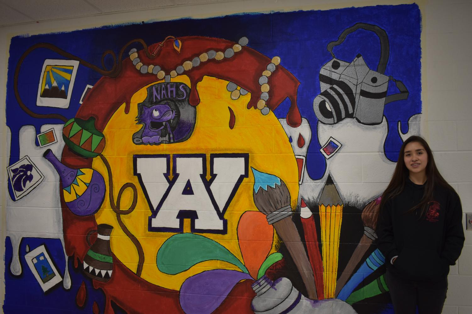 Larysa+Medina%2C+sophomore%2C+stands+in+front+of+the+mural+that+she+designed+with+National+Art+Honors+Society.+