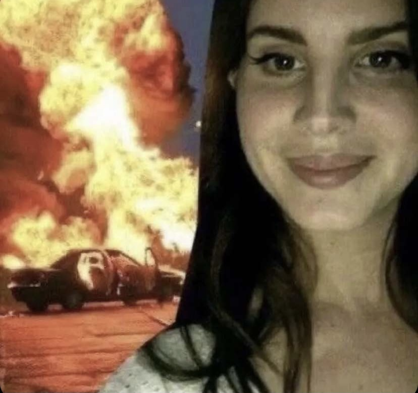 Edited photo of Lana Del Rey standing in front of a car on fire while smiling, quickly became the photo associated with the Lana Cult.